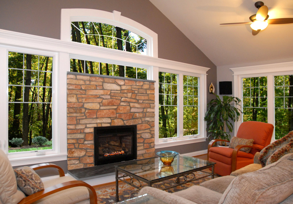 Home Remodeling Idea: Fireplace built within wall of windows to give outdoor view